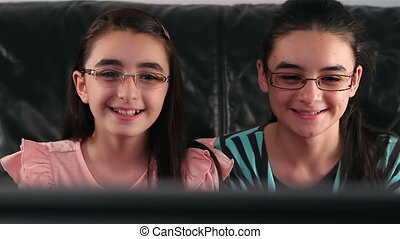 Happy teen girls watching tv - Happy teen girls with glasses...