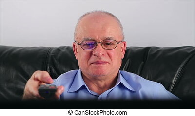 Senior man watching TV - Happy senior man with glasses and...
