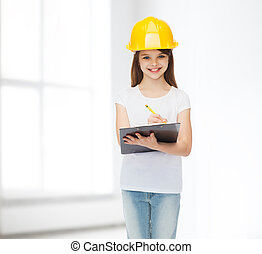 smiling little girl in hardhat with clipboard - childhood,...