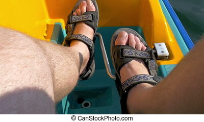 A mans feet paddling the water bicyle - A mans feet is...