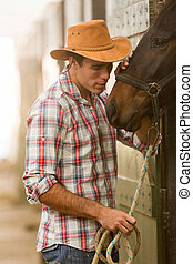 cowboy whispering to a horse - young cowboy whispering to a...