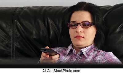 Young woman watching TV - Young woman with remote control...
