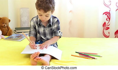 Little boy coloring at home