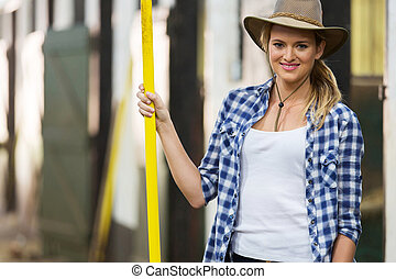 cowgirl holding a pitch fork inside stable - pretty cowgirl...