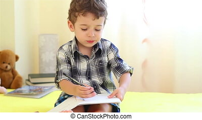 Little boy coloring with pencils at home