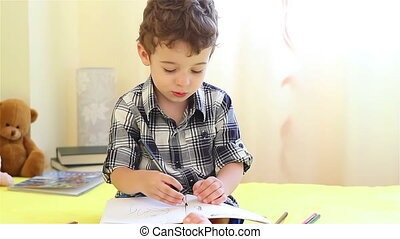 Little boy coloring in his bedroom
