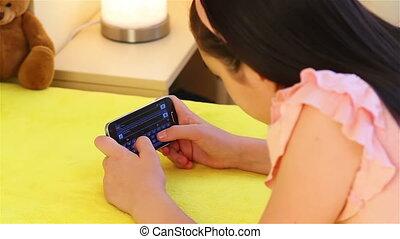 Teenage girl messages on smartphone - Preteen girl lying on...