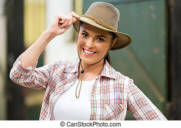 cowgirl holding hat - close up portrait of happy cowgirl...