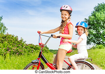 Two little girls sitting on a bicycle outdoors