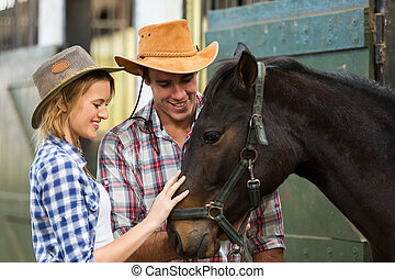 cowboy and cowgirl comforting a horse in stable