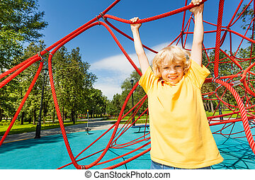 Positive boy with straight hands hangs on rope of playground...