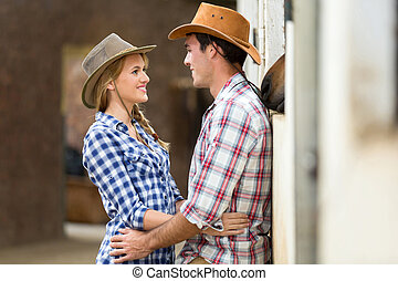 loving young couple inside stables looking at each other