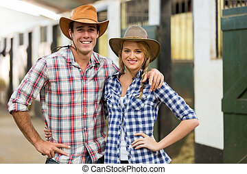 cowboy cowgirl couple inside stables - portrait of cowboy...