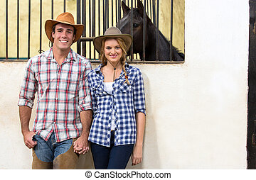 cowboy and cowgirl couple holding hands - happy cowboy and...