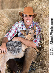 cowboy with his dog sitting on hay - portrait of cowboy with...