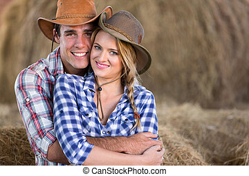 young farming couple hugging in barn - portrait of young...