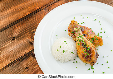 Baked chicken drumsticks with rise on wood table
