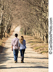 young couple walking on country road - back view of lovely...