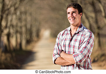 young man in autumn country road - happy young man with arms...