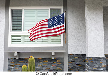 Flag on house - American flag blowing in the breeze while...