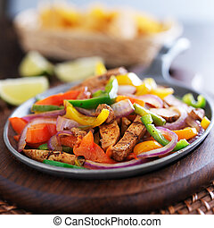 mexican chicken fajitas in iron skillet with peppers