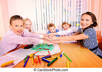 team work - Cheerful students sit at their desks during a...