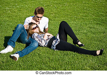 Young Couple Laying On Grass Field