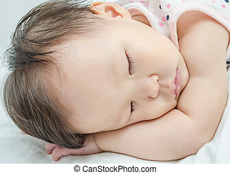 Asian baby girl sleeping on bed