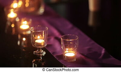 Burning candles on table - Group of burning candles cage on...
