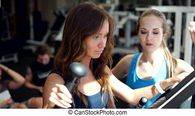 Using Elliptical Cross with a Coach - Young woman uses...