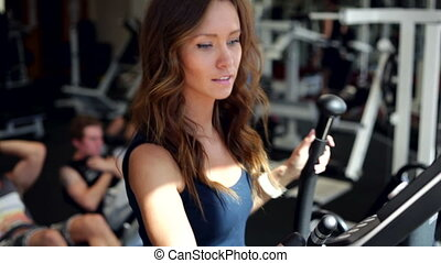 Using Elliptical Cross - Young woman uses elliptical cross...
