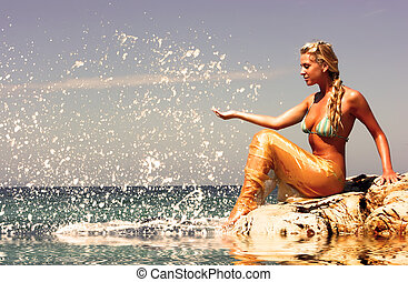 Mermaid at beach - Blonde mermaid sitting on the rocky beach