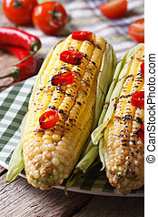 hot grilled corn with chili peppers close-up. vertical