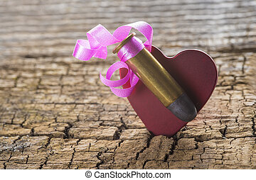 Bullet with a heart decorated like a gift on a wooden...