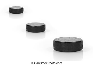 Three hockey puck in a row on a white background. Concept