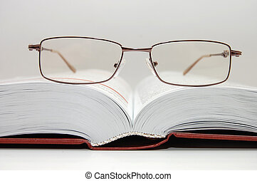 spectacles laying on the open book