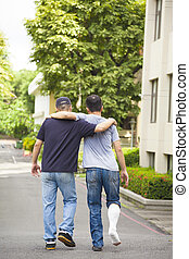 friend helping brothers or patient to walk without crutches...