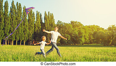 Dad and son child flying a kite in summer nature - happy...
