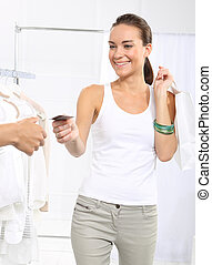 Purchases on credit. - Woman in clothing store pay for...