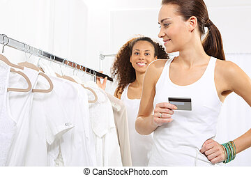 credit card - Woman in clothing store pay for purchases by...