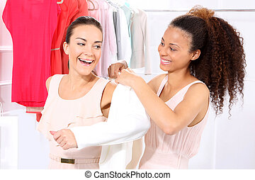 Women in clothing boutique - Two women shopping in boutique...