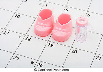 Baby Due Date - Pink baby booties and bottle on a calendar...