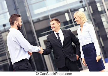 Business people greeting outside modern building