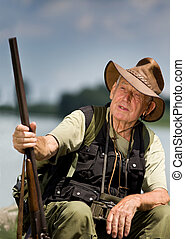 Hunter - Senior hunter with shotgun sitting beside lake