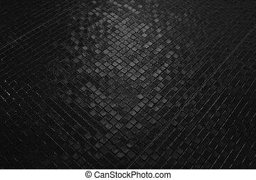 Dark tiles mosaic pattern on a wall