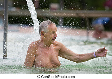 Water therapy - Senior man enjoying waterfall in hot water...