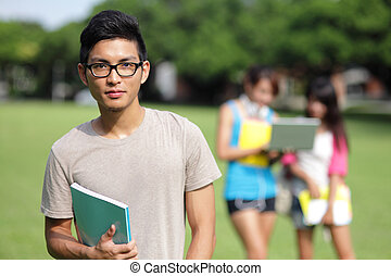 Happy College students smile to you on campus lawn, asian