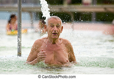 Water therapy - Senior man enjoying waterfall in hot water...