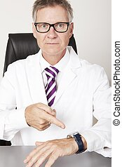 Serious Male Doctor Pointing Wrist Watch