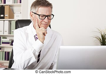 Medical Specialist Seriously Reading at Computer